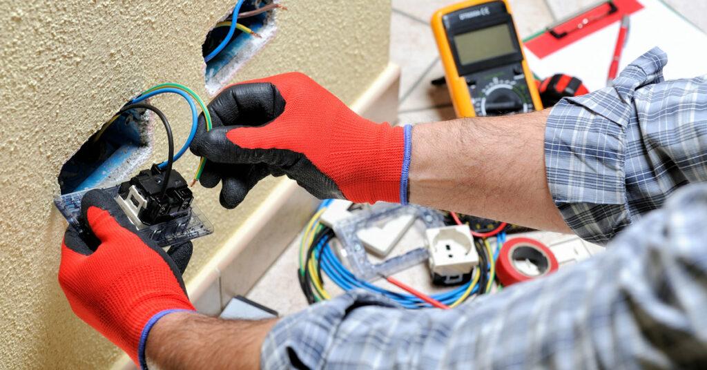 mies tekee sähköhuoltotöitä punaiset käsineet kädessä